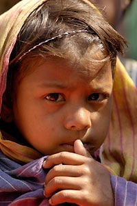 Young girl with a head covering, holding her thumb to her mouth