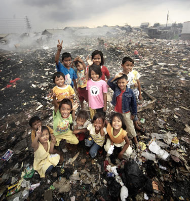 Several children stand happily on a large pile of trash at the city dump where they look for treasures.