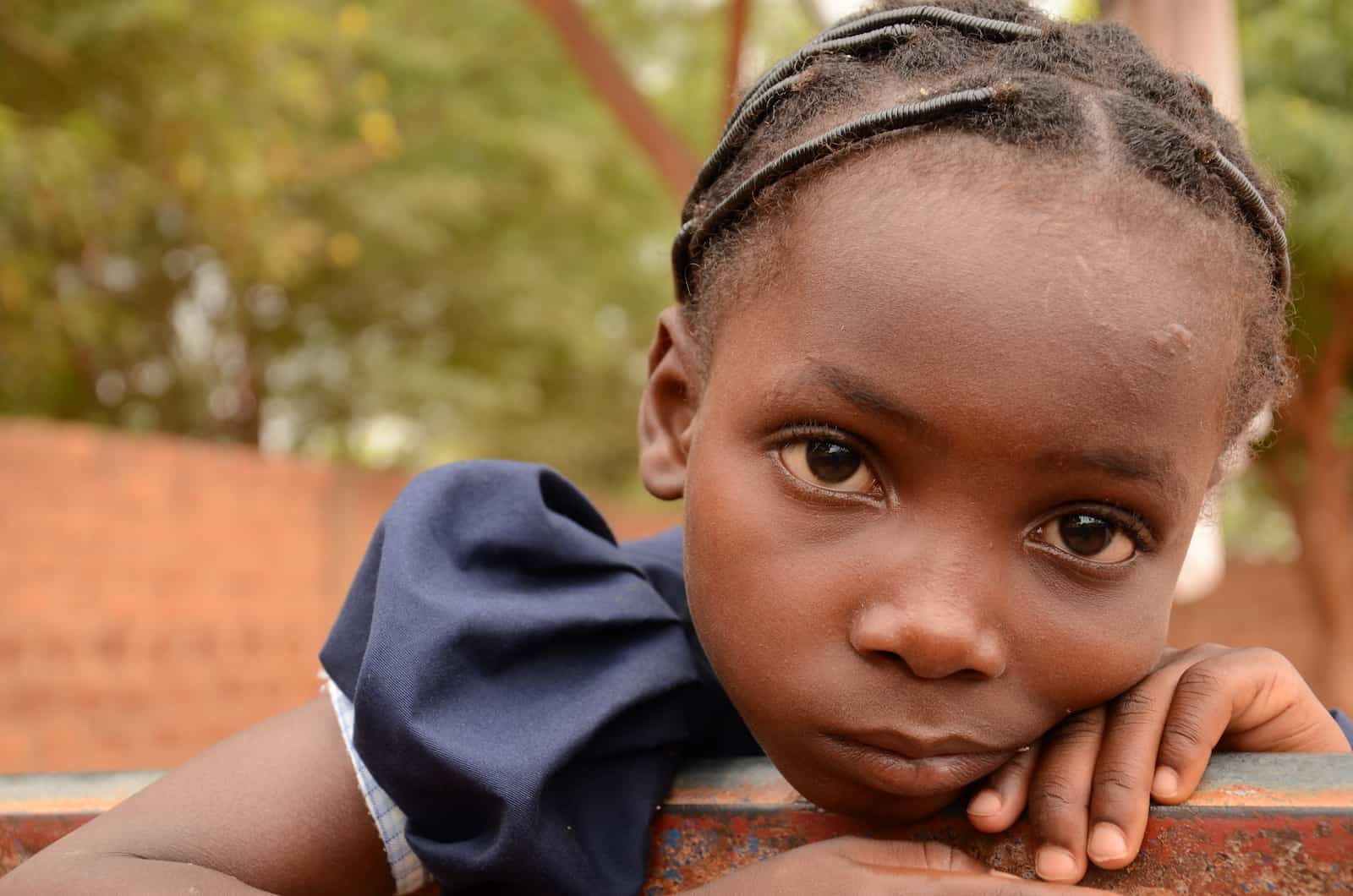 A tired girl leans on a fence in Burkina Faso