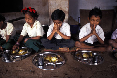 children praying before eating a meal