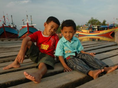 two boys sitting on dock