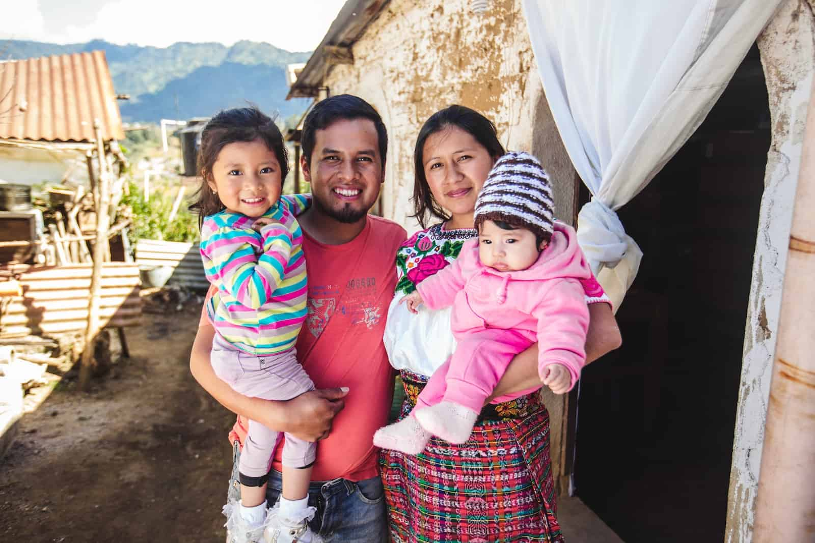 A family of four stands outside a brick home in Guatemala.