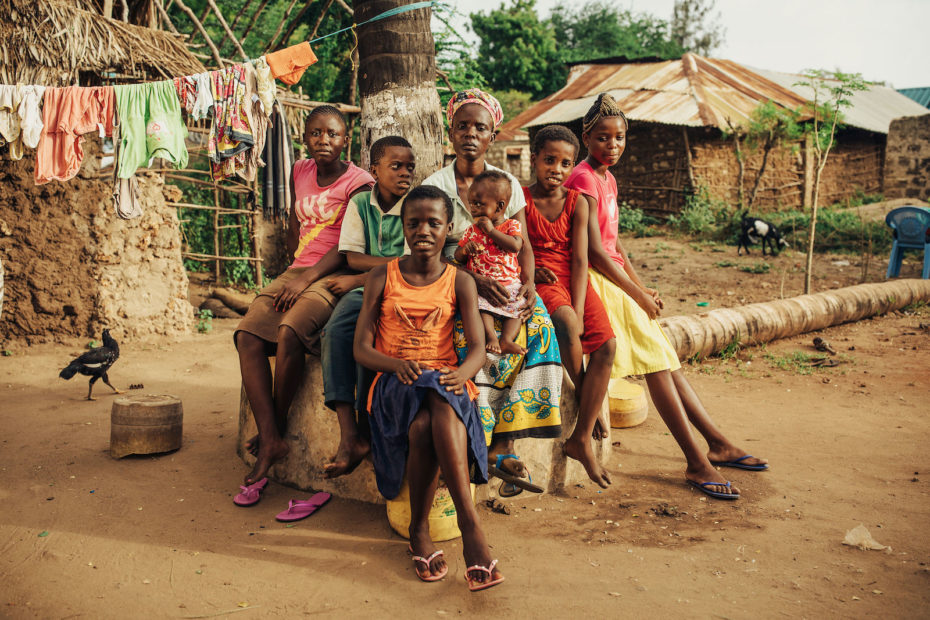 A large family sits outside of grass and mud homes in Kenya.
