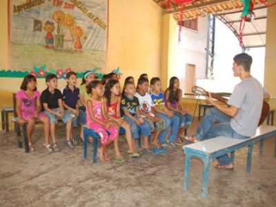Man sitting on a bench playing guitar for a group of children in a classroom
