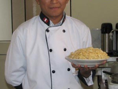 man in chef's uniform holding bowl of pasta