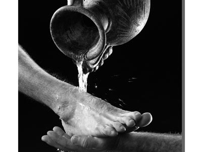 water pouring from jar over bare foot