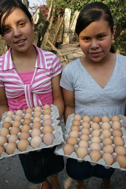 two girls holding cartons of eggs