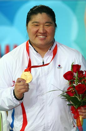 woman wearing gold medal and holding roses