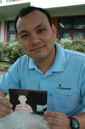 young man holding a photo of a child