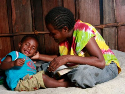 mother reading a book to a smiling little boy