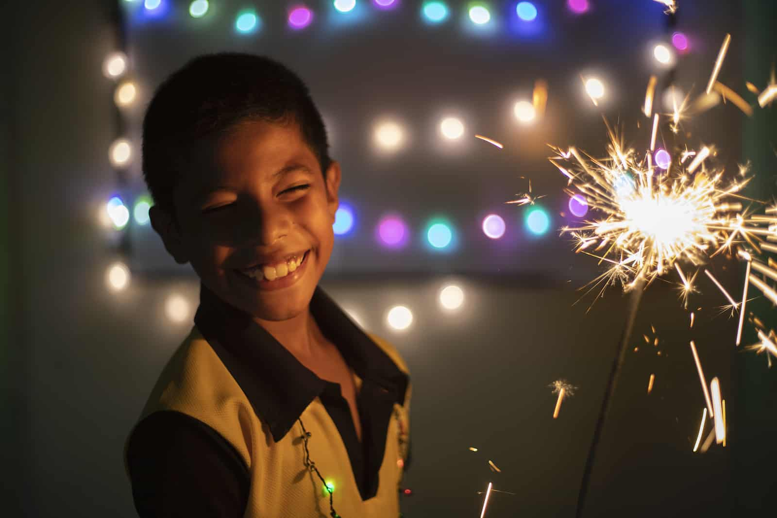 A boy holds a sparkler, surrounded by lights celebrating Christmas in El Salvador