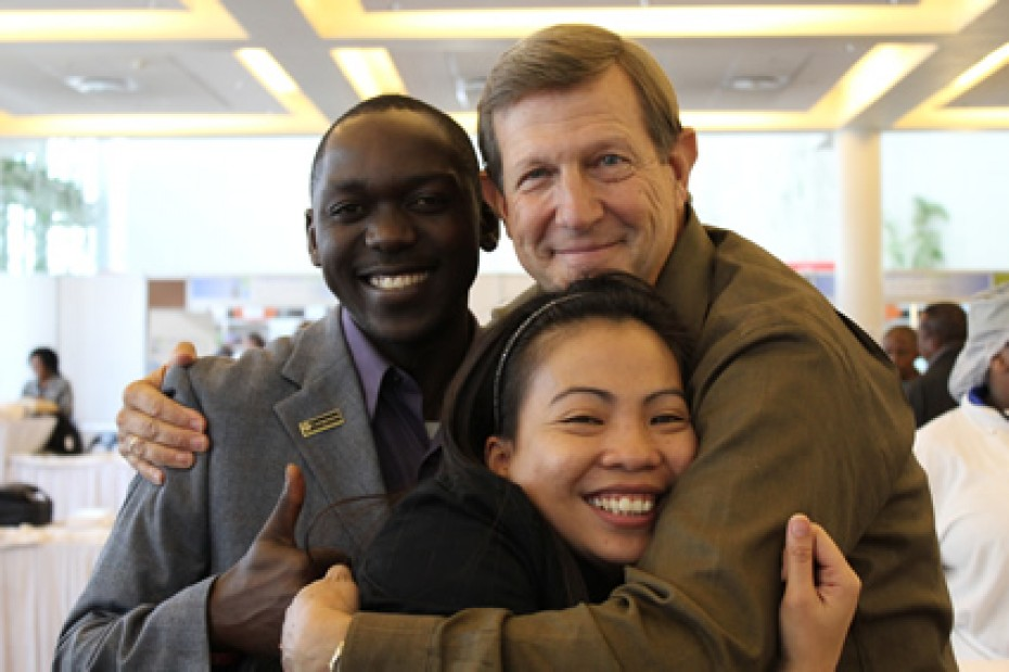 Wess Stafford embracing man and woman