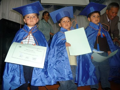 small children in caps and gowns holding diplomas