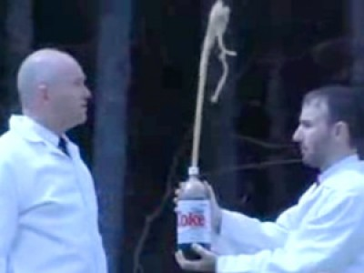 Two men with a large bottle of diet Coke.