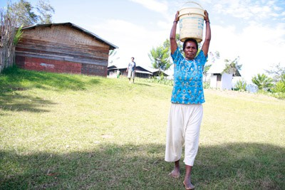 woman carrying pail of water on head