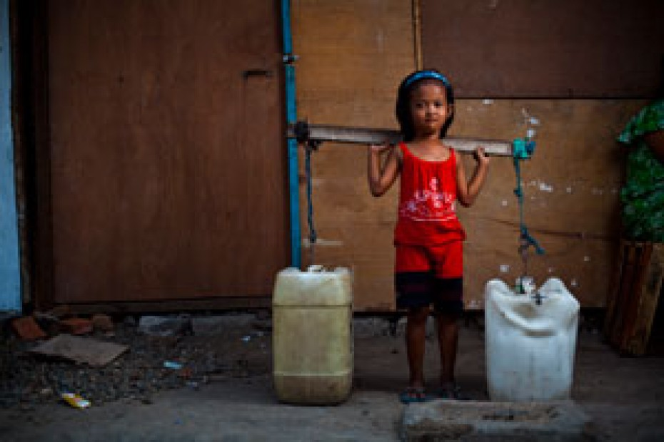 small girl carrying two large water containers