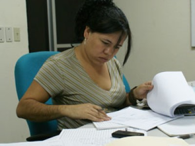 woman looking through paperwork at desk