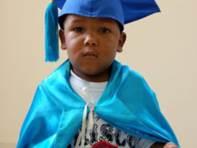 Young child in graduation cap and gown.