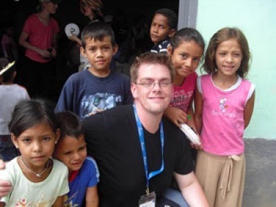 Several young children around a young man.
