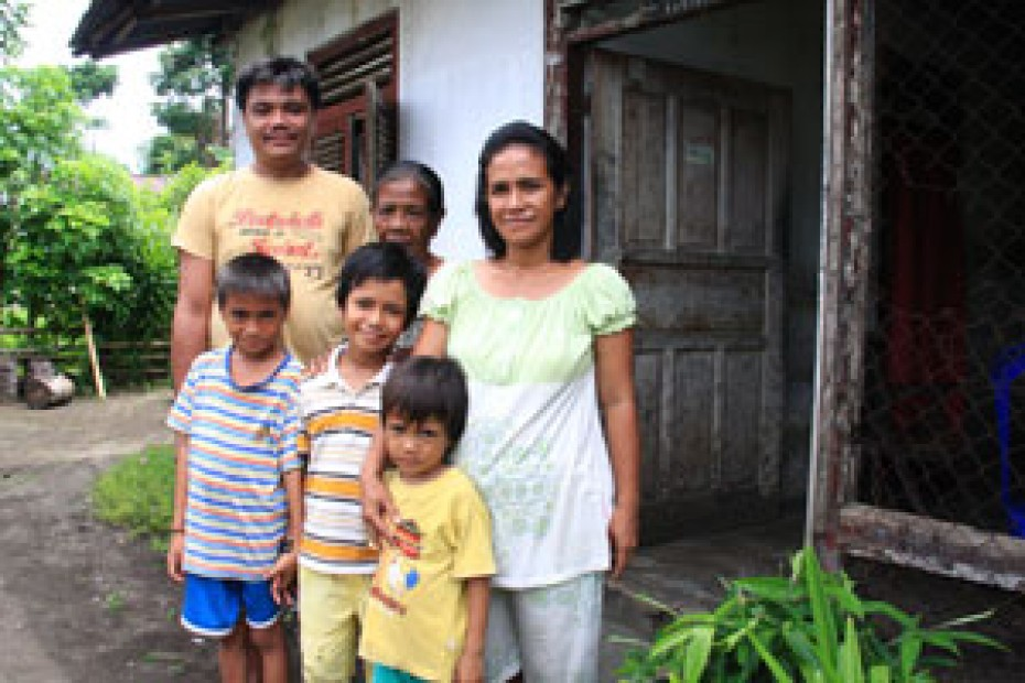family standing outside their home in Indonesia