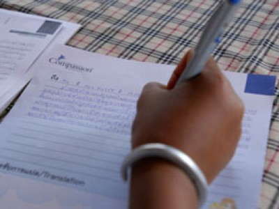 a hand holding a pen writing a Compassion letter