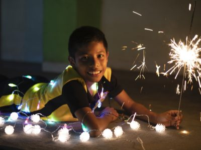A boy lays on the ground, holding a sparkler and surrounded by Christmas lights.