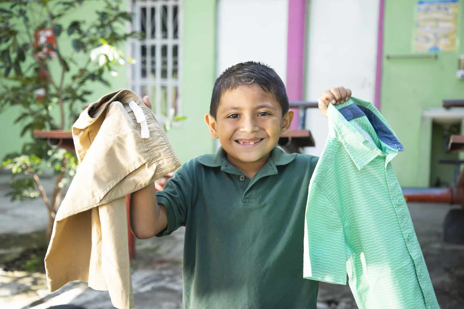 A boy holds up a shirt and pants, smiling.