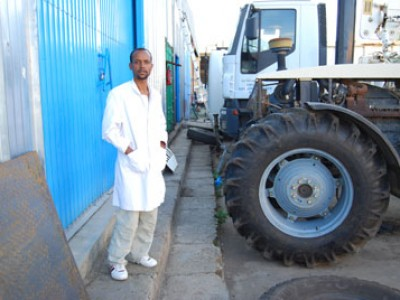 young man standing by tractor and large truck