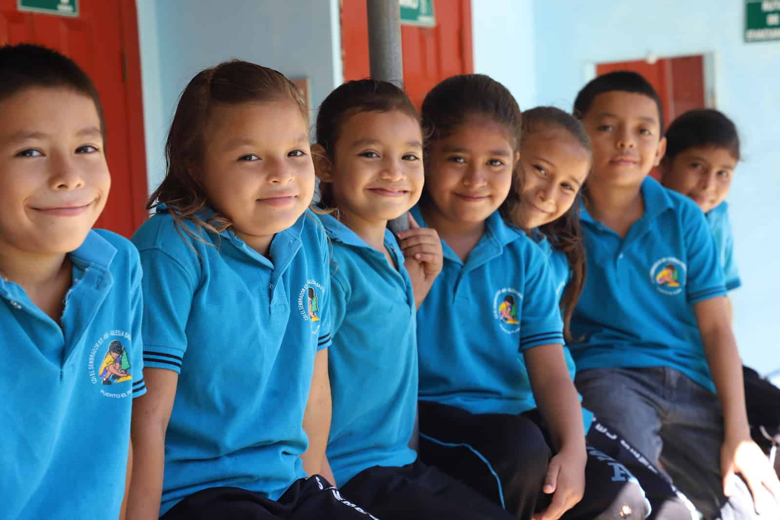 Children in blue shirts sit on a porch together.