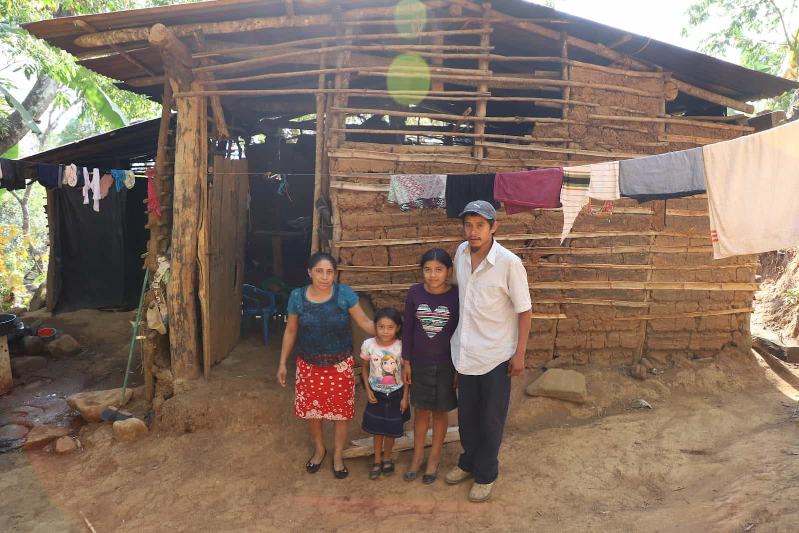 A family stands in front of a mud home in rural El Salvador