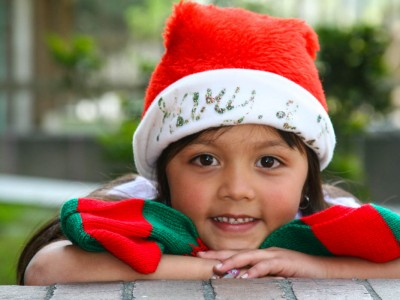 A cute smiling girl wearing a santa hat