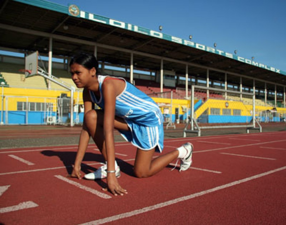 girl in starters position on running track