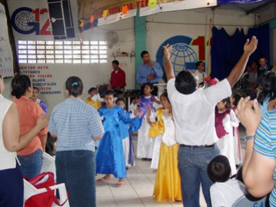 group of adults and children singing inside church building