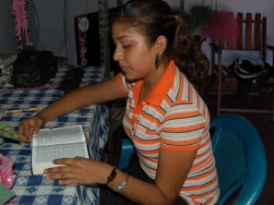 girl sitting at table reading Bible