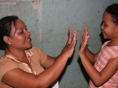 A woman and girl playing a game with their hands
