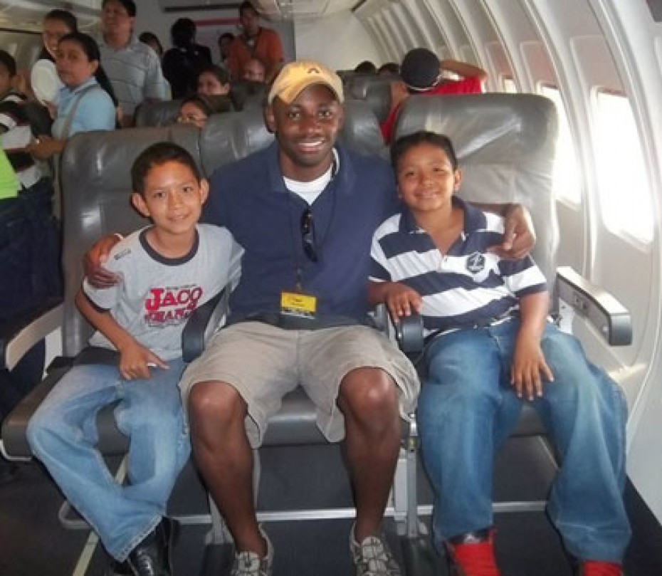 A man with two children sitting on a plane