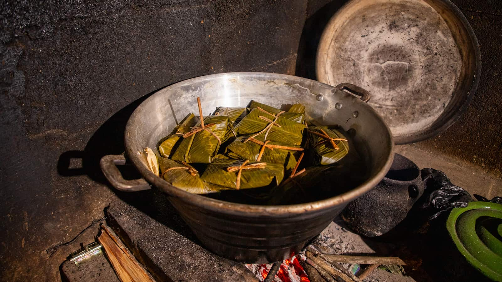 A metal bowl with leaf-wrapped tamales