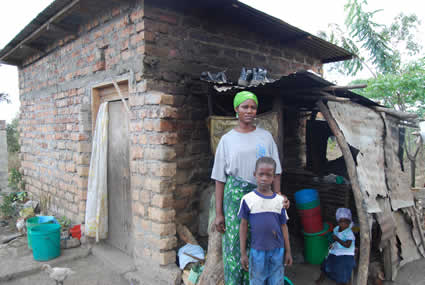 woman, boy and small child standing outside of house