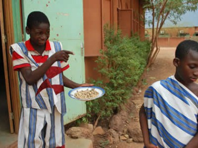 a boy in a red striped shirt carrying a plate of food pointing at another child