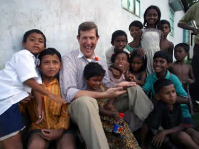 a man sitting up against a wall surrounded by happy children