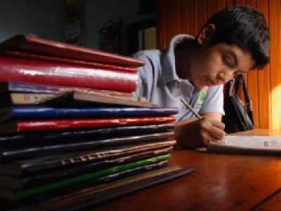 boy sitting and writing beside stack of books