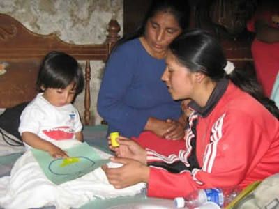 two women with a child looking at a paper