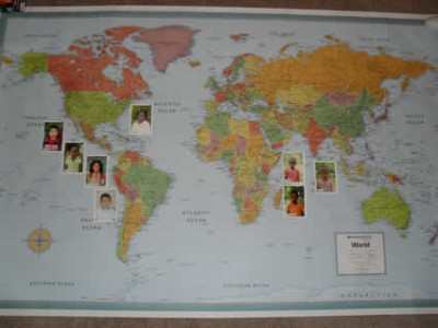 world map with children's photos attached