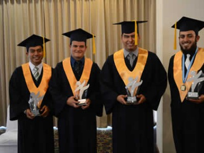 four male graduates posing for camera with awards