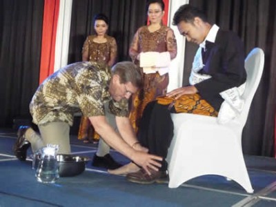 Wess Stafford washes the feet of a Leadership Development Program graduate on stage