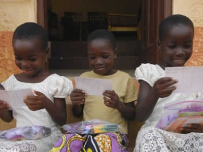 three young girls reading letters