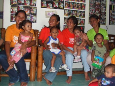 smiling women holding babies and young children