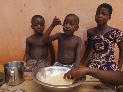 three children eating from large bowl