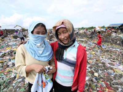 two women standing in garbage dump