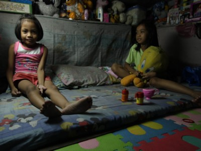 Two girls sitting on a mat playing
